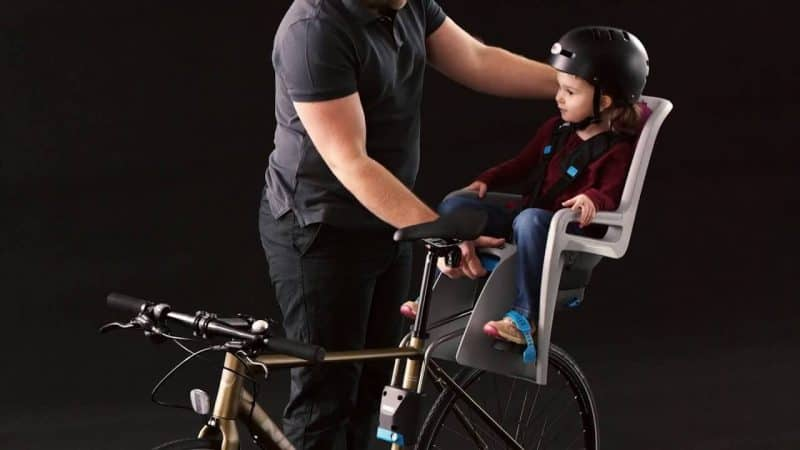 Child riding in THULE child bike seat RIDEALONG