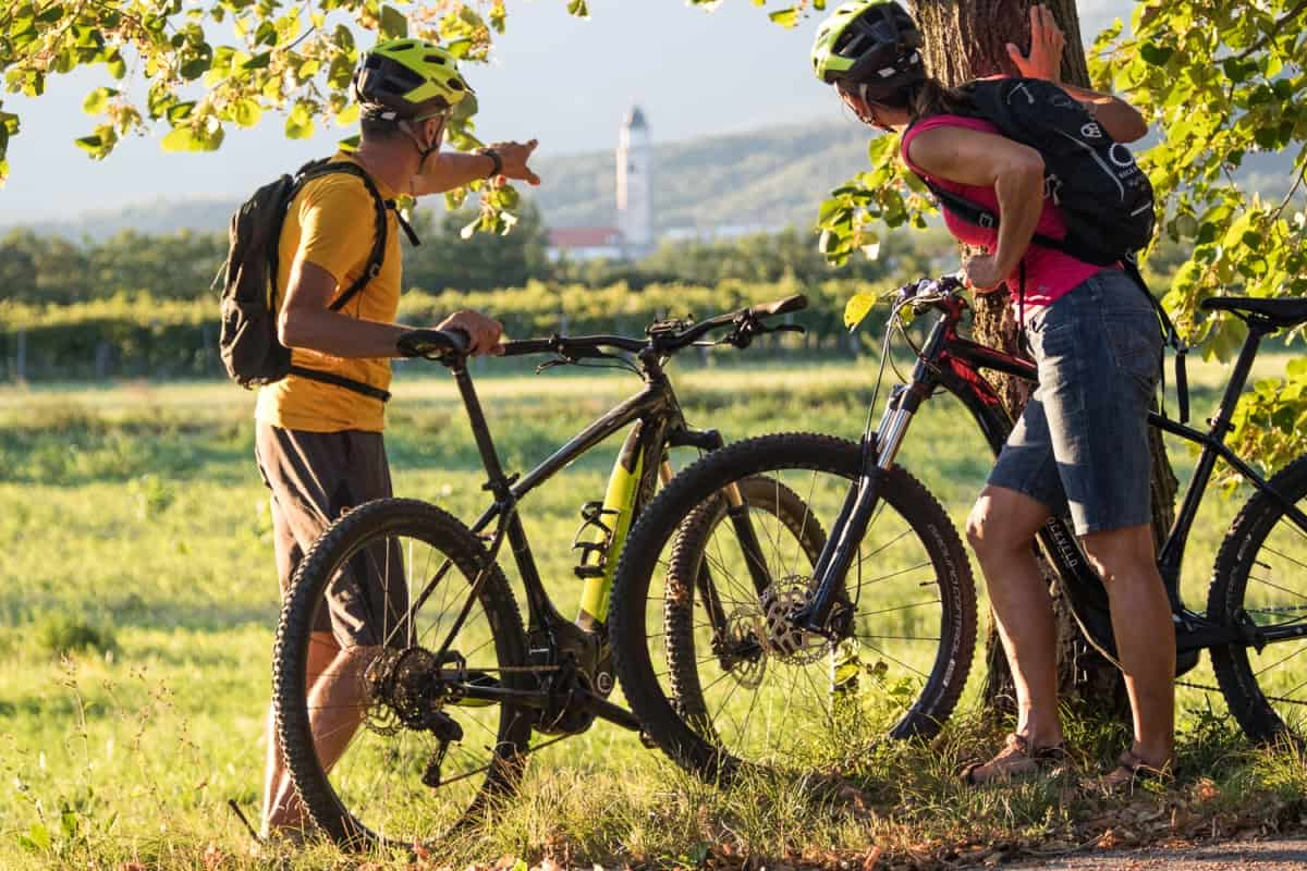 Cycling in Vipava Valley. Couple on electric mountain bikes exploring the green Slovenia. RockVelo rental bikes.