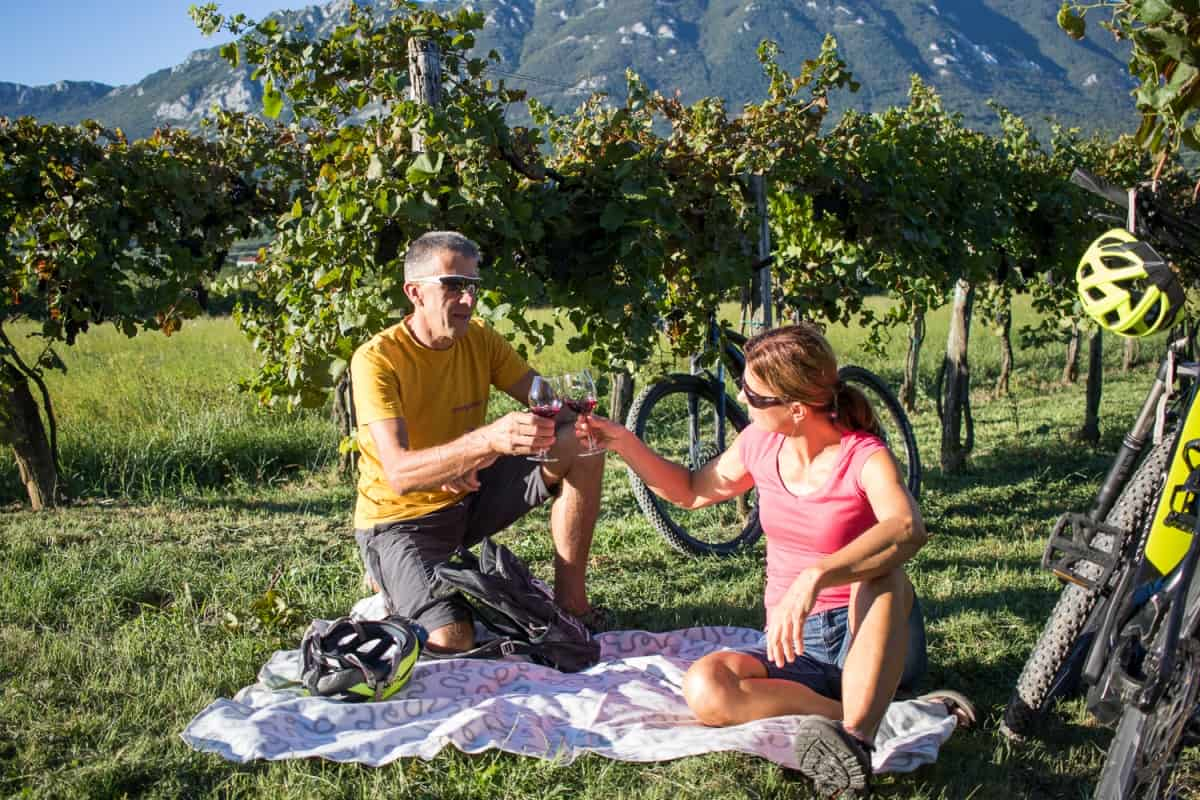 A couple enjoying wine in the middle of vineyards. Pick-nic style. E-bike tour of Vipava Valey by RockVelo.