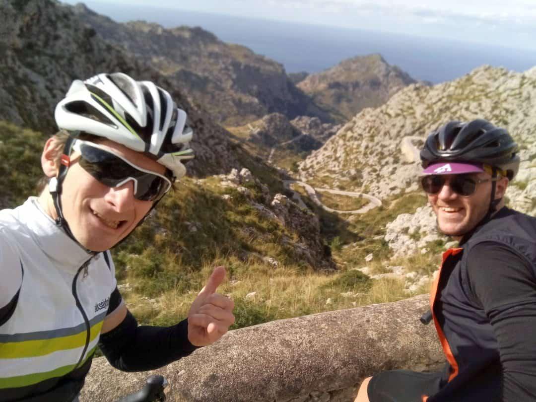 kolesarski vodič in kolesar na vrhu vzpona