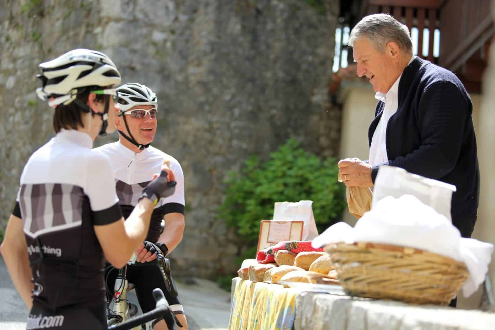 Slovenian people. Local selling bread at Štanjel village. Road cyclists touring Slovenia.