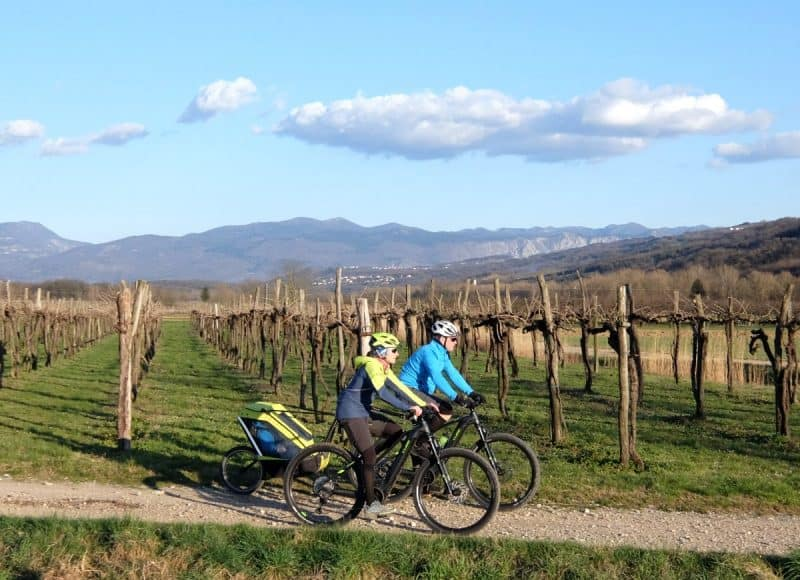 Couple cycling with ebikes and child bike trailer. Photo by RockVelo tours Slovenia